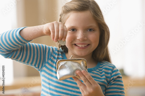 Caucasian girl putting coin into purse