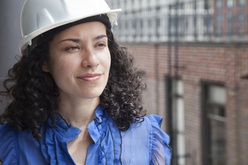 Smiling Hispanic businesswoman wearing hard-hat