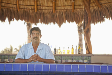 Hispanic bartender standing behind bar