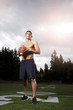 Hispanic athlete holding football