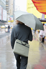 Caucasian businessman walking in rain with umbrella