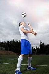 Hispanic athlete heading soccer ball