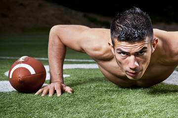 Hispanic man doing push-ups near football