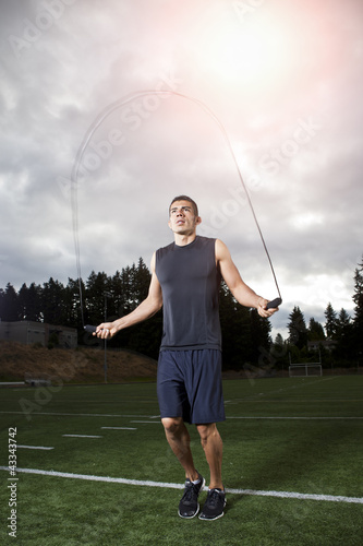 Hispanic man jumping rope on field