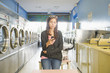 Hispanic woman using cell phone in self-service laundry facility