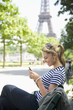 Hispanic woman using cell phone near Eiffel Tower