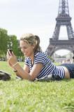 Hispanic woman using cell phone in park near Eiffel Tower