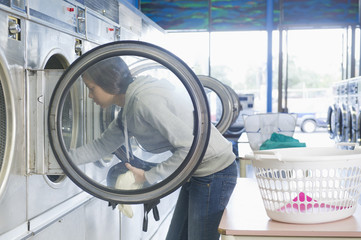 Hispanic woman doing laundry in self-service laundry facility