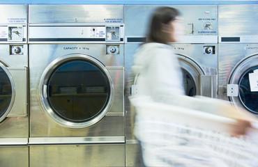 Hispanic woman doing laundry in self-service laundry facility