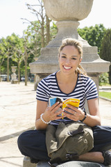 Hispanic woman looking at guide book in park
