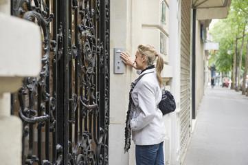 Hispanic woman pressing buzzer on city street