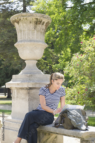 Hispanic woman looking at map in park