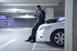 Caucasian businessman sitting on car in parking garage