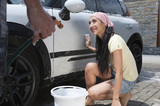 Hispanic couple washing car together
