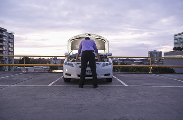 Caucasian businessman checking underneath automobile hood