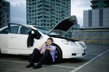 Caucasian businessman sitting near car having car trouble