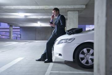 Caucasian businessman sitting on car in parking garage