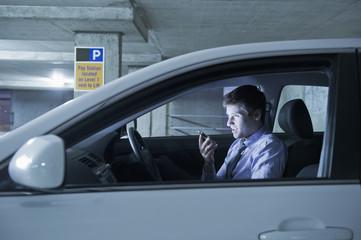 Caucasian businessman using cell phone in car