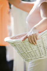 Caucasian woman holding basket and hanging laundry