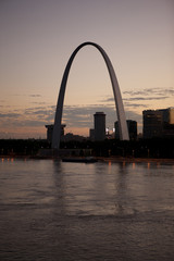 Arch landmark next to urban river at sunset