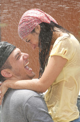 Hispanic couple getting squirted with water