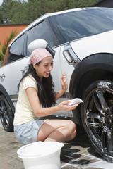 Smiling Hispanic woman washing car