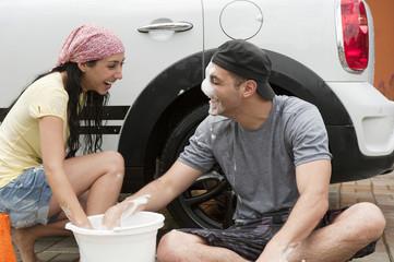 Playful Hispanic couple washing car together
