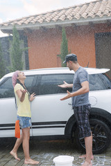 Rain falling on Hispanic couple washing car