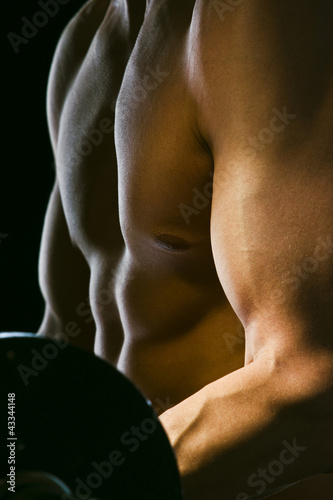 Caucasian man exercising with barbells