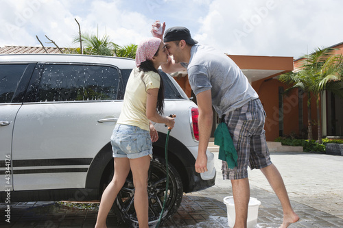 Hispanic couple kissing and washing car together