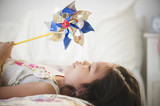 Korean girl laying on bed holding pinwheel