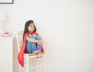 Korean girl in cape sitting on chair