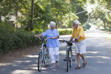 Senior Caucasian couple pushing bicycles on street