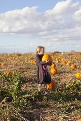 Caucasian girl carrying pumpkin in field