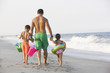 Father and children holding hands on beach