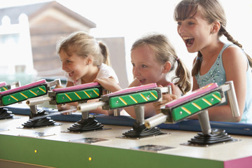 Caucasian girls playing at amusement park arcade