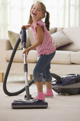 Laughing girl vacuuming living room floor