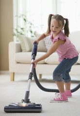 Girl vacuuming living room floor