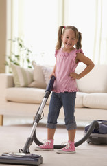 Grinning girl vacuuming living room floor