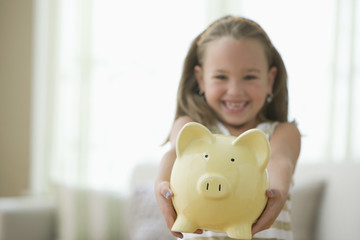 Grinning girl holding out piggy bank