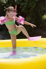 Girl in snorkel gear getting into kiddie pool