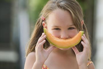 Girl holding a wedge of cantaloupe
