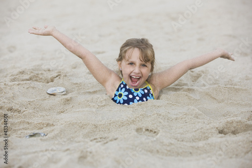 Caucasian girl buried in the sand on beach