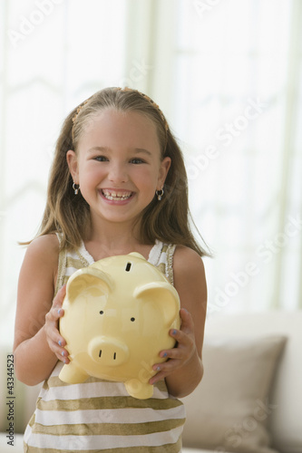 Grinning girl holding piggy bank