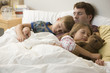 Caucasian father and children sleeping in bed together