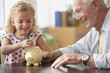 Caucasian grandfather watching granddaughter putting coin into piggy bank