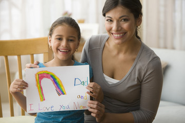 Daughter giving rainbow drawing to mother