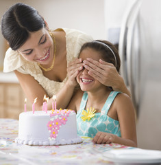 Mother covering daughter's eyes near birthday cake