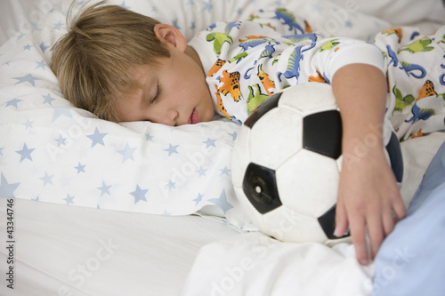 Caucasian boy sleeping in bed with soccer ball