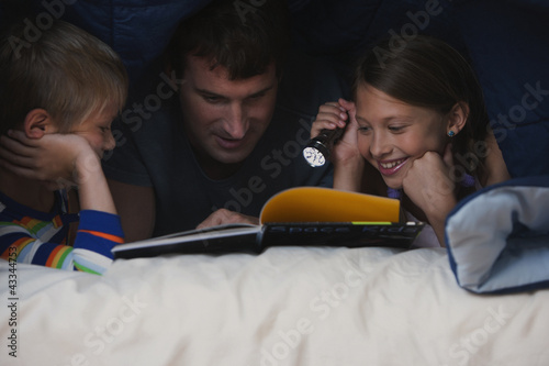 Caucasian father and children reading book under covers